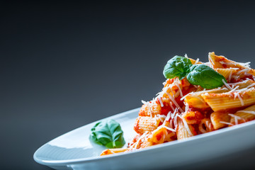 Pasta Penne with Tomato Bolognese Sauce, Parmesan Cheese and Basil Leaves. Mediterranean food.Italian cuisine.