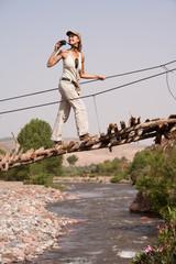 femme souriant faisant des photos sur un petit pont en bois