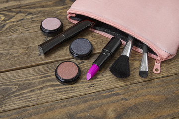 A pink make up bag with beauty products spilling on a rustic wooden background, forming a page border
