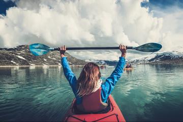 Woman kayaking on Styggvatnet glacier lake near Jostedalsbreen glacier.