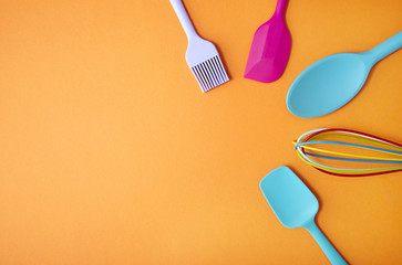 Colorful kitchen utensils arranged on an orange background forming a page border