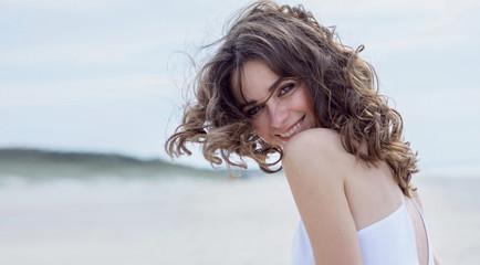 Красивая счастливая женщина на пляже. Портрет крупным планом. Фотография смеющейся  девушки на берегу моря. Ветер развевает волосы.