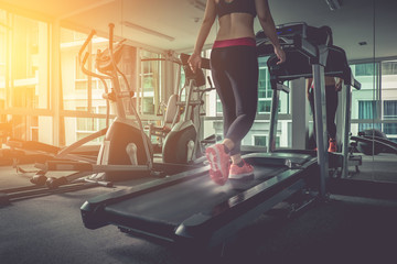 Woman running in a gym on a treadmill concept for exercising, fi