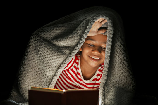 Cute girl reading book at night