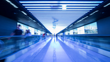 People going in walkway and riding flat escalators at the airport of Seoul, South Korea. Futuristic blue toned shot