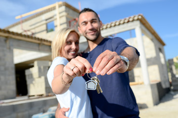 cheerful young happy couple holding home keys in front of contruction site of new house