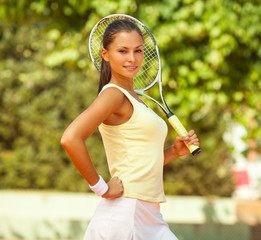 Attractive female tennis player standing on tennis court and looking at camera. Recreational tennis player.