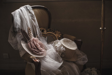 Bride's hats on arm-chair with white wedding dress