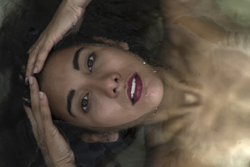 Sensual woman with bright lips in water