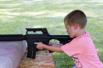 Young boy practicing proper gun safety and use.