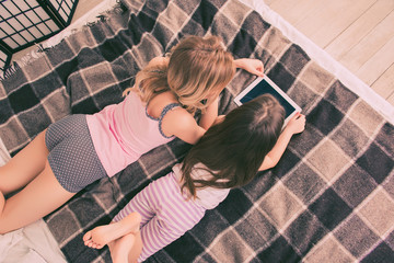 Top view of of small daughter and mother lying on bed with table
