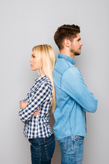 Serious man and woman with crossed hands standing back to back