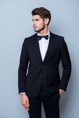Serious sexy man in black suit holding hand in pocket