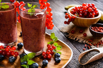 Fresh juicy smoothies with red currants, blueberry, banana, goji berries and chia seeds in a glass jar
