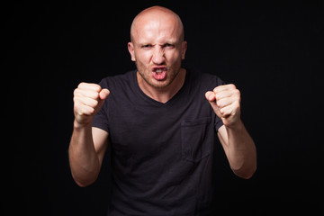Close up portrait of an angry bald man, shaking his fists, black background