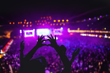 heart shaped hands showing love at festival. Silhouette against concert Lights background