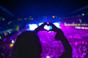 heart shaped hands at concert, woman at festival loving the artist and the music
