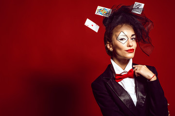 Portrait of a young beautiful lady croupier with an artistic make up joker and flying cards around on the red background. Gamble and casino concept. Studio shot. Copy-space Wall mural