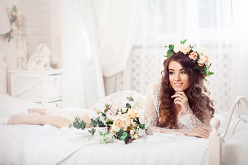 Morning sexy bride with bouquet lying on a bed dressed in white nighty and wreath. Horizontal. Image released.
