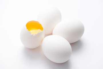 four fresh, free range, white, organic eggs. one broken with selective focus, close up, isolated on white background and horizontal