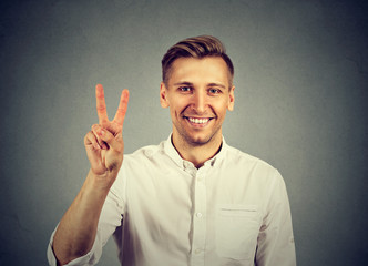 young handsome man holding up peace victory, two sign
