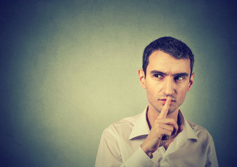 Suspicious man giving Shhhh quiet, silence, secret gesture