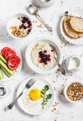 Assortment of breakfast - oatmeal with berries, fried egg, fresh vegetables, cottage cheese, yogurt and berries, homemade granola on a light table. Healthy food. Top view