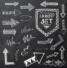 Hand drawn arrow icons set on black chalk board.