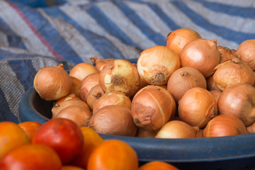 The group of onion in the tray on the table in the market