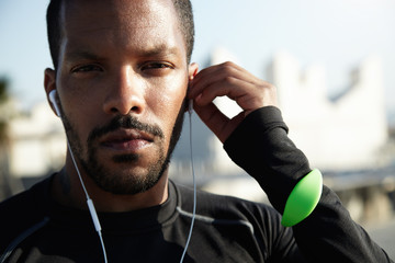 Cropped shot of attractive runner with muscular athletic body dressed in black sportswear resting after physical activities in open air. Young jogger listening to meditative music with earphones