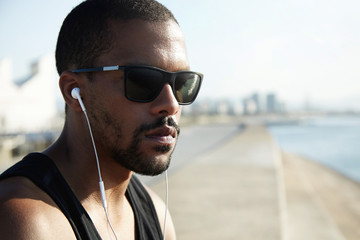 Dark-skinned male in stylish sunglasses sitting on pavement at sea enjoying summertime, contemplating sunrise, thinking, meditating, listening to music with headphones, looking far away, dreaming