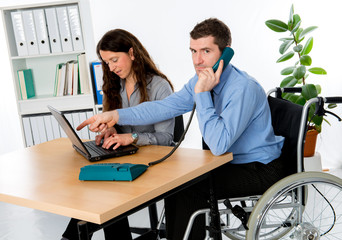 disabled business man in wheelchair and his female colleague
