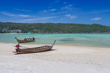 Long tail boat on the beach with mountain background
