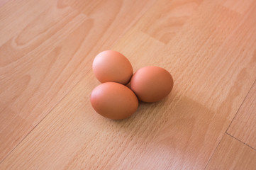 Group of three hen egg on wooden table/ floor background