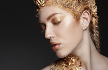 Portrait of beautiful sexy model with gold foil on her face