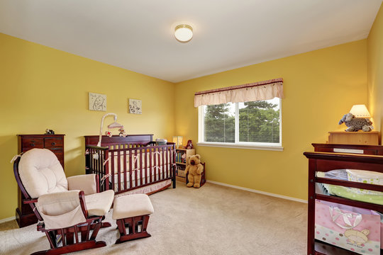 Cute yellow nursery room with comfortable rocking chair.