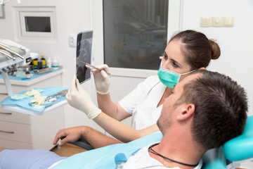 Image of young patient and dentist showing him x-ray radiography, in the Dental Clinc