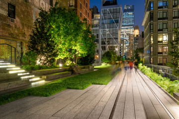 The High Line promenade illuminated at twilight surrounded by modern and older buildings in Chelsea. The aerial greenway is also known as Highline or High Line Park. Manhattan, New York CIty