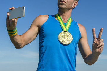 Brazilian gold medal athlete standing against blue sky using his mobile phone to take a selfie