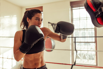 Female boxer punching focus pads