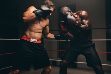 Two boxers fighting on boxing ring
