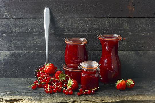 Marmelade im Glas mit frischen Beeren,  rustikaler Hintergrund