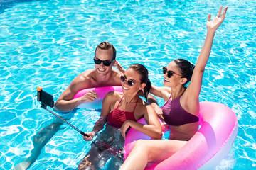 Joyful friends making selfies in a swimming pool
