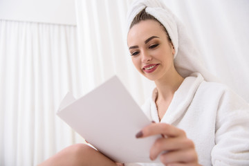 Cute girl reading magazine at beauty salon