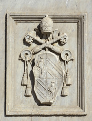 Relief of Pope Pius IX emblem on a monument erected in Tiberina Island (Rome) and made by sculptor Jacometti in 1869