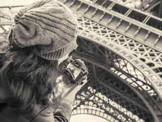 Girl taken pictures Eiffel Tower.