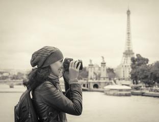 Girl taken pictures Eiffel Tower.