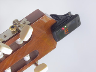 headstock of the guitar with installed clip-on tuner, that shows