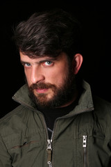 Bearded man in khaki jacket with interesting look. Close.up. Black