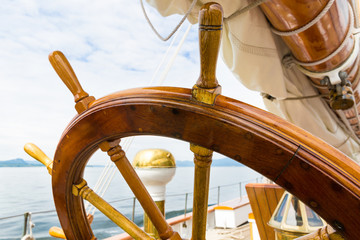 Wooden wheel of a big sailboat at sea. Close up nautical detail
